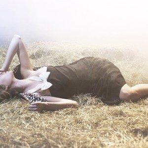 Fashion fotografie door Olger Grandia. Kleur foto van blond model Marleen Emke, liggend in stro, hooibaal.